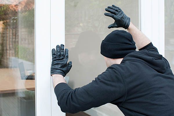A bad guy trying to break into a home with safety window film.