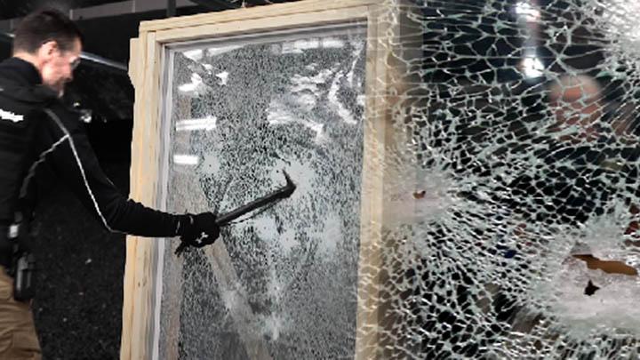 A still image of a man smashing through unprotected glass.